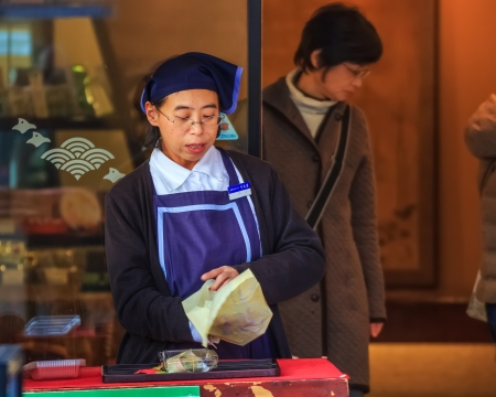 shop keeper: NARA, JAPAN - NOVEMBER 16  Japanese sweet in Nara, Japan on November 16, 2013   Unidentified female shop keeper wraps her sweet with paper for tourists at Sanjo-dori street