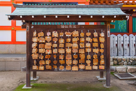 ema: Ema - small wooden plaques which Shinto worshippers write their prayers then leave hanging at the Shrine, in Ikuta-jinja Shrine