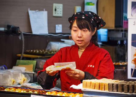 shop keeper: Kyoto, Japan - November 19 2013  Unidentified female shop keeper sells a pack of japanese sweets to herf customer at Arashiyama