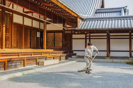rokuonji: KYOTO, JAPAN - NOVEMBER 20  Kinkaku-ji in Kyoto, Japan on November 20, 2013  Unidentified japanese worker prepares the rock for the garden in front of a temple