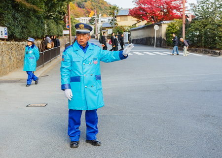 KYOTO, JAPAN - NOVEMBER 20  Security Guard in Kyoto, Japan on November 20, 2013  Unidentified security guard operates the traffic in front of Kinkaku-ji Temple