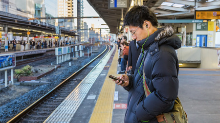TOKYO, JAPAN - NOVEMBER 22  People on a platform in Tokyo, Japan on November 22, 2013  Unidentified Japanese male uses his device while waits for a train on a plateform