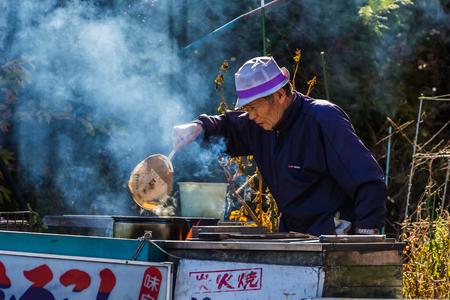 kawaguchi ko: KAWAGUCHIKO, JAPAN - NOVEMBER 22  Senior citizen in Kawaguchiko, Japan on November 22, 2013  Unidentified senior male sets fire boiling corn in the kettle to sell to tourist on the side of the road Editorial