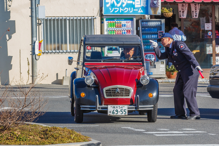 KAWAGUCHIKO, JAPAN - NOVEMBER 23  Security Guard in Kawaguchiko, Japan on November 23, 2013  Unidentified Japanese security guard informs direction to the driver