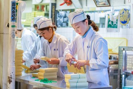 distributing: TOKYO, JAPAN - NOVEMBER 25  Tsukiji fish market in Tokyo, Japan on November 25, 2013  Unidentified japanese workers pack the food before distributing to customer