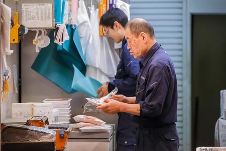 TOKYO, JAPAN - NOVEMBER 25  Tsukiji fish market in Tokyo, Japan on November 25, 2013  Unidentified japanese workers pack the food before distributing to customer