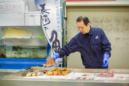 TOKYO, JAPAN - NOVEMBER 25  Tsukiji fish market in Tokyo, Japan on November 25, 2013  Unidentified japanese fish seller categorizes fish before selling to people