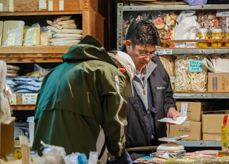 shop keeper: TOKYO, JAPAN - NOVEMBER 25  Tsukiji fish market in Tokyo, Japan on November 25, 2013  Unidentified grocery shop keeper sell his product to his customer early in the morning