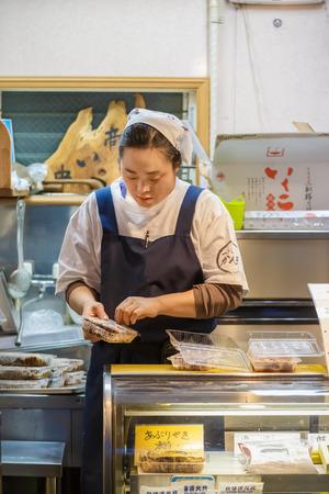 shop keeper: TOKYO, JAPAN - NOVEMBER 25  Tsukiji fish market in Tokyo, Japan on November 25, 2013  Unidentified japanese workers pack the food before distributing to customer