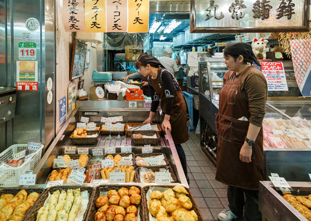 shop keeper: KYOTO, JAPAN - OCTOBER 23: Nishiki Market in Kyoto, Japan on October 23, 2014. Unidentified Japanese shop keeper prepares products in the shop for customer Editorial