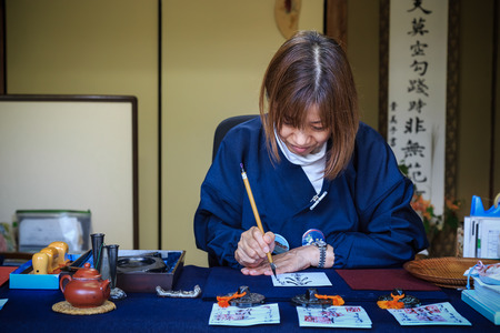 japan calligraphy: KYOTO, JAPAN - OCTOBER 21: Religious Volunteer in Kyoto, Japan on October 21, 2014. Unidentified Religious Volunteer writes calligraphy on a paper for using as a talisman in Ssisho-in temple Editorial
