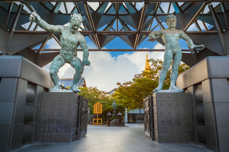benevolent: Osaka, Japan - October 24 2014: Modern bronze statues of Nio Benevolent Kings stand guard at the gate in front of Isshinhji Temple Editorial