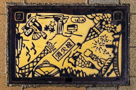 manhole cover: KOBE, JAPAN - OCTOBER 26: Manhole Cover in Kobe, Japan on October 26, 2014. Signs and symbols of important places that represent Kobe put down onto a manhole along a street in Kobe city Editorial