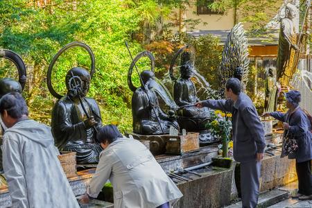 personas banandose: Templo Okunoin con Cementerio Area en Koyasan (Mt. Koya) en Wakayama Wakayama, Jap�n - 29 de octubre: Templo Okunoin en Wakayama, Jap�n, el 29 de octubre de 2014. La gente no identificada que ba�an el Buda en frente del templo Okunoin