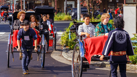 tokyo: TOKYO, JAPAN - NOVEMBER 15, 2015: Unidentified rickshaw drivers with passengers in Asukusa station nearby Sumida river