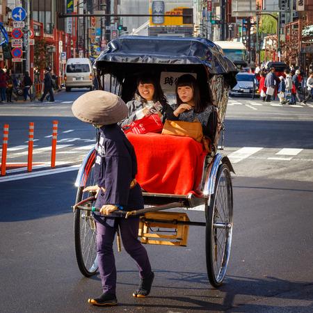 rikscha: TOKYO, JAPAN - NOVEMBER 15, 2015: Unidentified rickshaw drivers with passengers in Asukusa station nearby Sumida river
