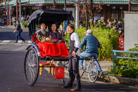rikscha: Tokyo, Japan - 15. November 2015: Nicht identifizierte Rikscha-Fahrer mit Passagieren in Asukusa Station in der Nähe Sumida-Fluss