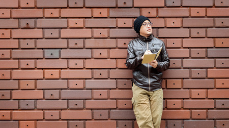 jot: An Asian Man in a Brown Jacket with a Small Notebook in His Hands Stock Photo