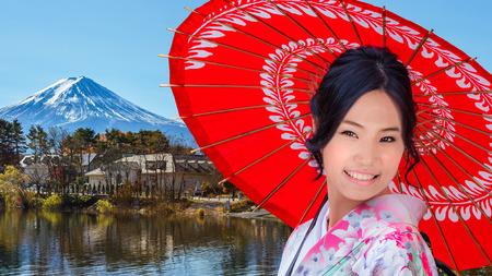 koyo: Young Japanese Woman with Mt. Fuji at Lake Kawaguchiko Stock Photo