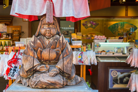 priestess: MIE, JAPAN - NOVEMBER 20, 2015: Wood sculpture of Japanese priestess at Oharai-machi is the old-800 meter long pilgrimage road that leads to Ise Jingu inner shrine with traditional Edo architecture style