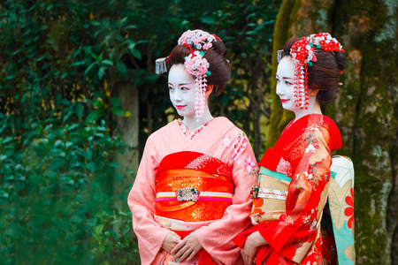 maiko: Geisha - Maiko in Gion District in Kyoto, Japan   KYOTO, JAPAN - NOVEMBER 22 2015: Unidentified Maiko girl - apprentice Geisha in western Japan, especially Kyoto. Their jobs consist of performing songs, dances, and playing the shamisen (Japanese string