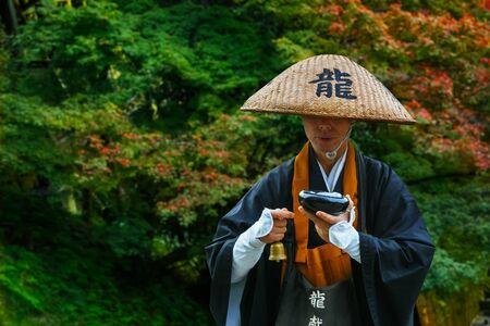 KYOTO, JAPAN - NOVEMBER 22 2015: Unidentified Japnese monk prays for passing people in front of Kiyomizu-dera temple Redactioneel