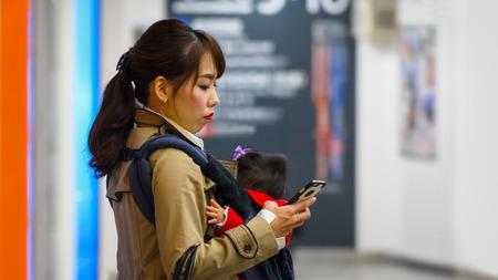 femal: YOKOHAMA, JAPAN - NOVEMBER 24 2015: Unidentified Japanese mother with her baby
