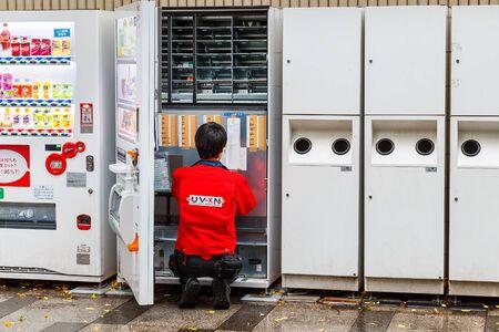TOKYO, JAPAN - NOVEMBER 25 2015: Unidentified Japanese prepares beverage for a vending machine