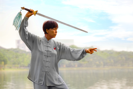 chuan: BANGKOK, THAILAND - FEBRUARY 20, 2016: Unidentified group of people practice Chinese sword with Tai Chi Chuan in a park Editorial