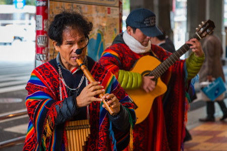 TOKYO, JAPAN - NOVEMBER 26 2015: Unidentified group of Peruvian Street Musicians perform traditional music for people at Uneno station