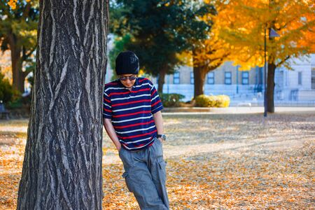 An Asian Man Stands under a Yellow Ginkgo Tree in Autumn