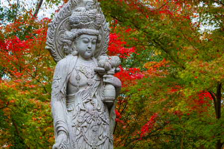 Stone Chinese Godess statue (Quanyim) at Eikando Zenrinji Temple in Kyoto, Japan  KYOTO, JAPAN - NOVEMBER 22 2015: Stone Chinese Godess statue (Quanyim) at Eikando Zenrinji Temple
