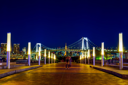 TOKYO, JAPAN - NOVEMBER 27 2015: Rainbow Bridge connects Odaiba to the rest of Tokyo. The two story bridge is an iconic symbol of the bay and is especially beautiful during its nightly illumination.