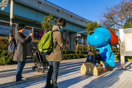 headquaters: TOKYO, JAPAN - NOVEMBER 27 2015: Unidentified Japanese families with a cartoon dog statue in front of Fuji Television Headquaters building in Odaiba area Editorial