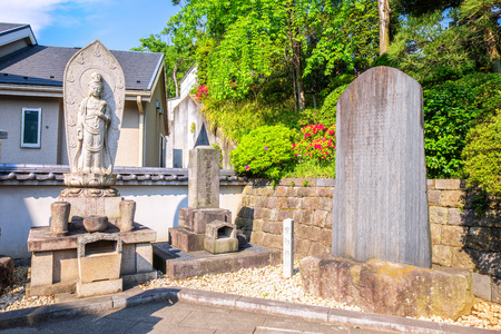 TOKYO, JAPAN - APRIL 20 2018: Tombs and religious statue at Sengakuji Temple