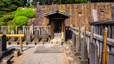 TOKYO, JAPAN - APRIL 20 2018: The grave of Oishi Kuranosuke  the leader of 47 ronin, the 47 loyal masterless samurai, one of the most popular Japanese historical epic legends at Sengakuji Temple