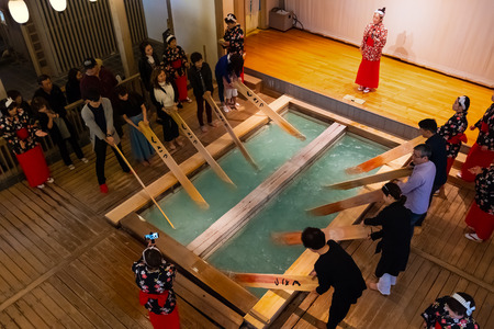 GUNMA, JAPAN - APRIL 27 2018: Yumomi is a traditional way to cool down Kusatsu's hot spring water to bathing temperature without diluting it with cold water