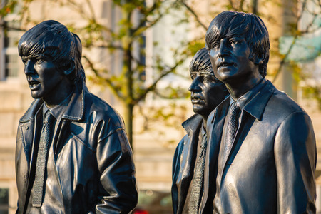 Liverpool, UK - May 17 2018: Bronze statue of the  Beatles stands at the Pier Head on the side of River Mersey, sculpted by Andrew Edwards and erected in December 2015 Reklamní fotografie - 112207737