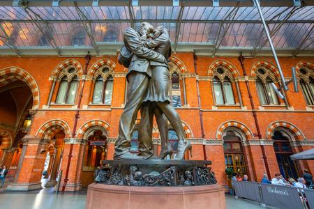 London, UK - 14. Mai 2018: Der Treffpunkt, 9 Meter hohe Bronzestatue, die 2007 enthüllt wurde, steht am südlichen Ende der oberen Ebene des Bahnhofs St. Pancras des britischen Künstlers Paul Day