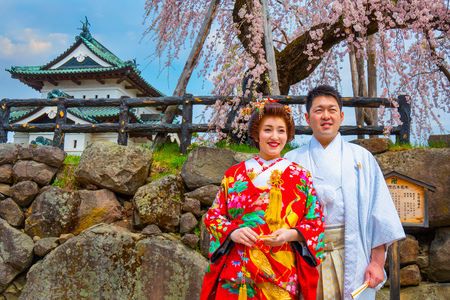 Hirosaki, Japan - April 23 2018: Unidentified Japanese gloom and bride attend a Japanese traditional wedding ceremony at Hirosaki Park in full bloom cherry blossom period