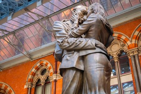 London, UK - May 14 2018: The Meeting Place, 9-metre bronze statue revealed in 2007, stands at the south end of the upper level of St Pancras railway station by British artist Paul Day