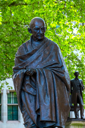 London, UK - May 13 2018: Statue of  Mahatma Gandhi at the Parliament Square with other twelve statues of statesmen and other notable individuals