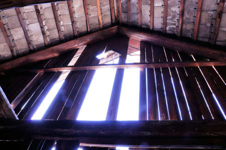 powerful light shining through wooden planks