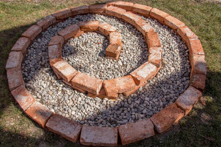 building herbal spiral first layer completed with small pebbles and soil