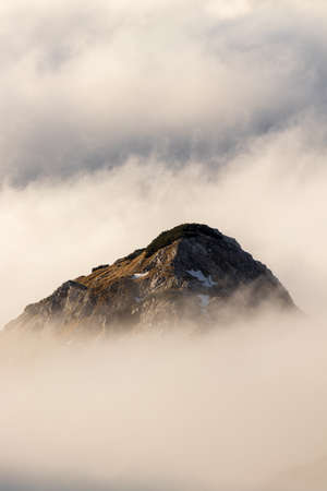 mountain peak looking above clouds