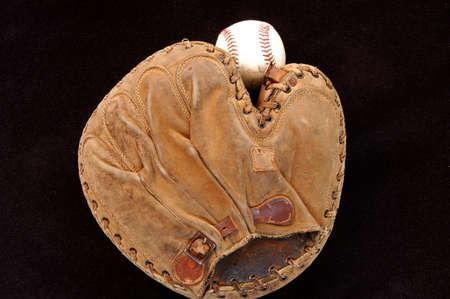 very old catchers mitt and baseball on black 스톡 콘텐츠