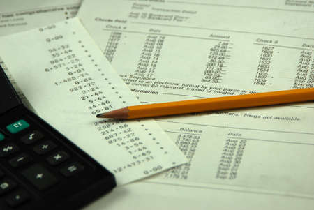 balancing business bank statement with pencil and calculator