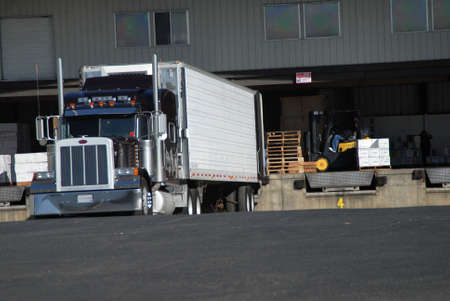 semi truck at fruit warehouse being loaded Stock Photo