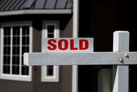 relocate: sold sign in front of new house