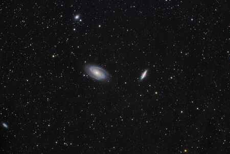 Real photo with two galaxies. They are Messier 81 and Messier 82 (Cigar galaxy). Galaxies are in Ursa Major constellation. Photo taken with the help of a long exposure of many frames